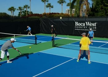 Residents playing a game of Pickleball on two of Boca West's Pickleball courts