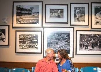 Couple seated on old Shea Stadium baseball seats at Grand Central at Boca West