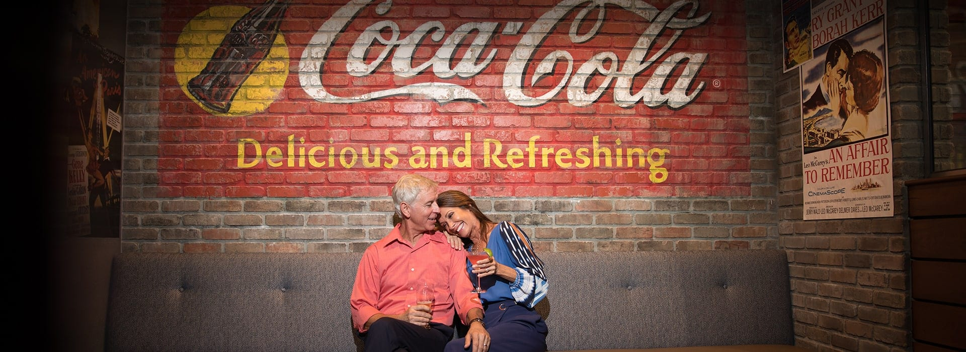 A couple sitting on a bench in Boca West's Grand Central with a Coca Cola mural behind them